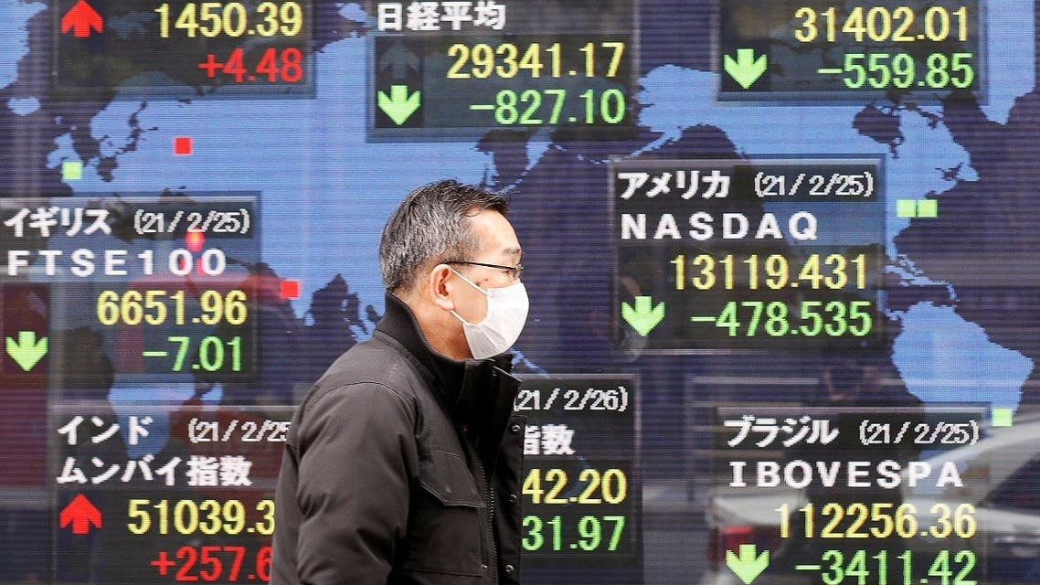 A man walks past a stock quotation board at a brokerage in Tokyo, Japan, on February 26, 2021. (Reuters)