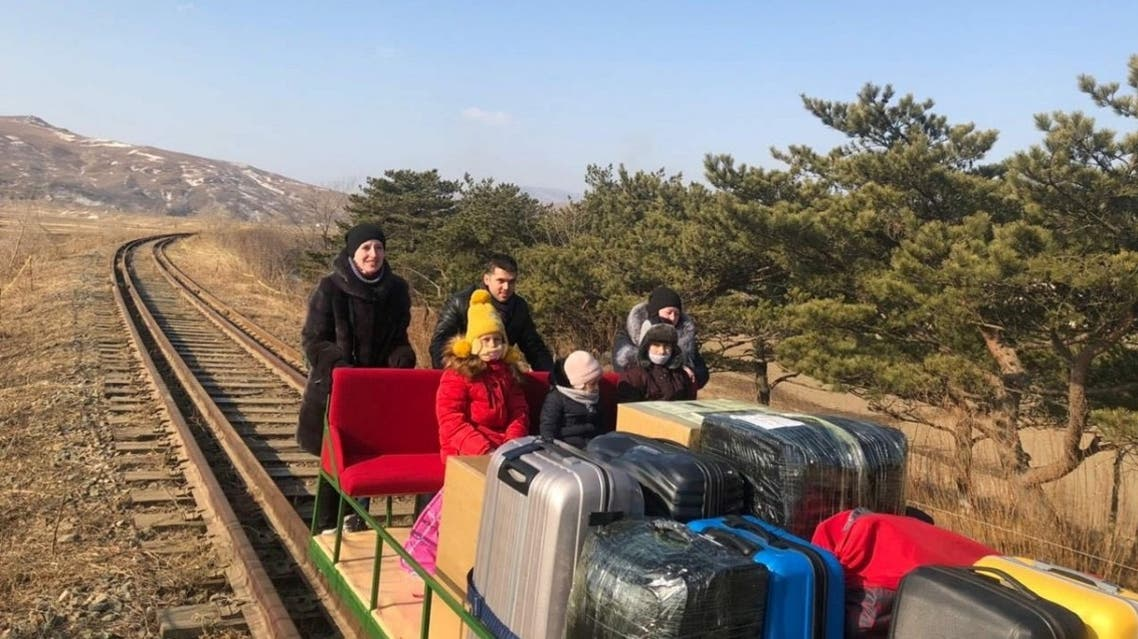 Russian diplomats and family members use a hand-pushed rail trolley to leave North Korea amid the coronavirus disease restrictions while crossing the demarcation line between North Korea and Russia. (Reuters)