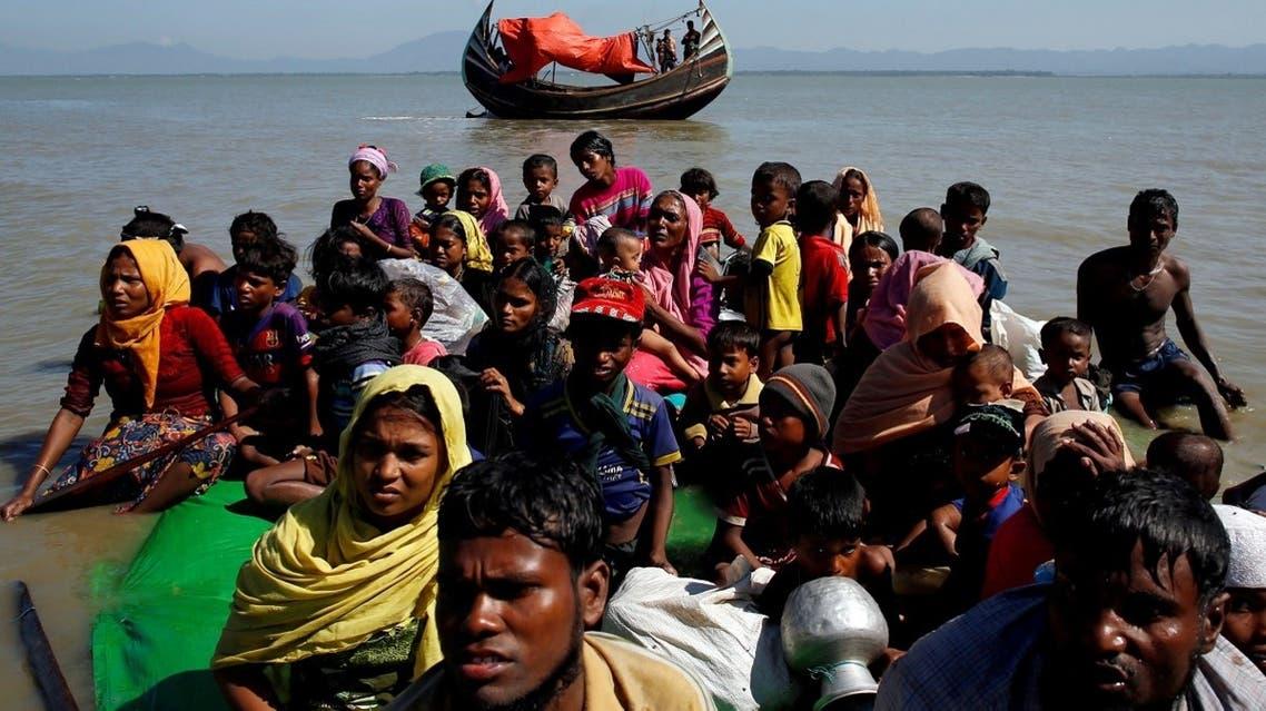 Rohingya refugees sit on a makeshift boat as they get interrogated by the Border Guard Bangladesh after crossing the Bangladesh-Myanmar border, at Shah Porir Dwip near Cox's Bazar, Bangladesh. (Reuters)