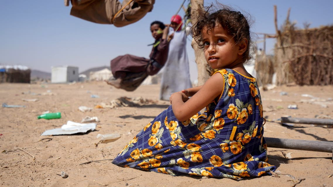 A girl sits as other children play on swings at a camp for internally displaced people in Marib, Yemen February 16, 2021. REUTERS/Nabeel al-Awzari NO RESALES. NO ARCHIVES TPX IMAGES OF THE DAY