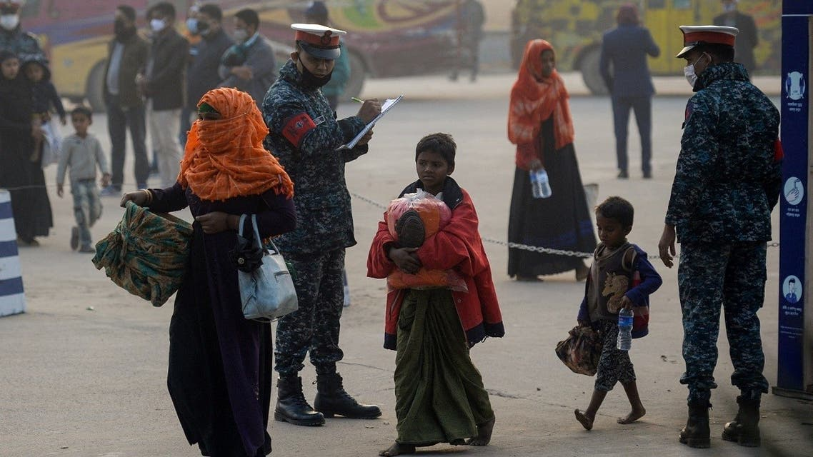 Rohingya refugees carry their belongings in Chittagong on January 30, 2021 as they make their way to a Bangladeshi navy ship that will take them to be relocated to Bhashan Char island in the Bay of Bengal. (Munir Uzzaman/AFP)