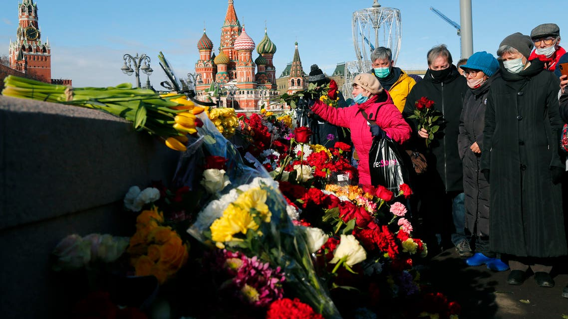A woman lays flowers near the place where Russian opposition leader Boris Nemtsov was gunned down, in Moscow, Russia, Saturday, February 27, 2021. (AP)