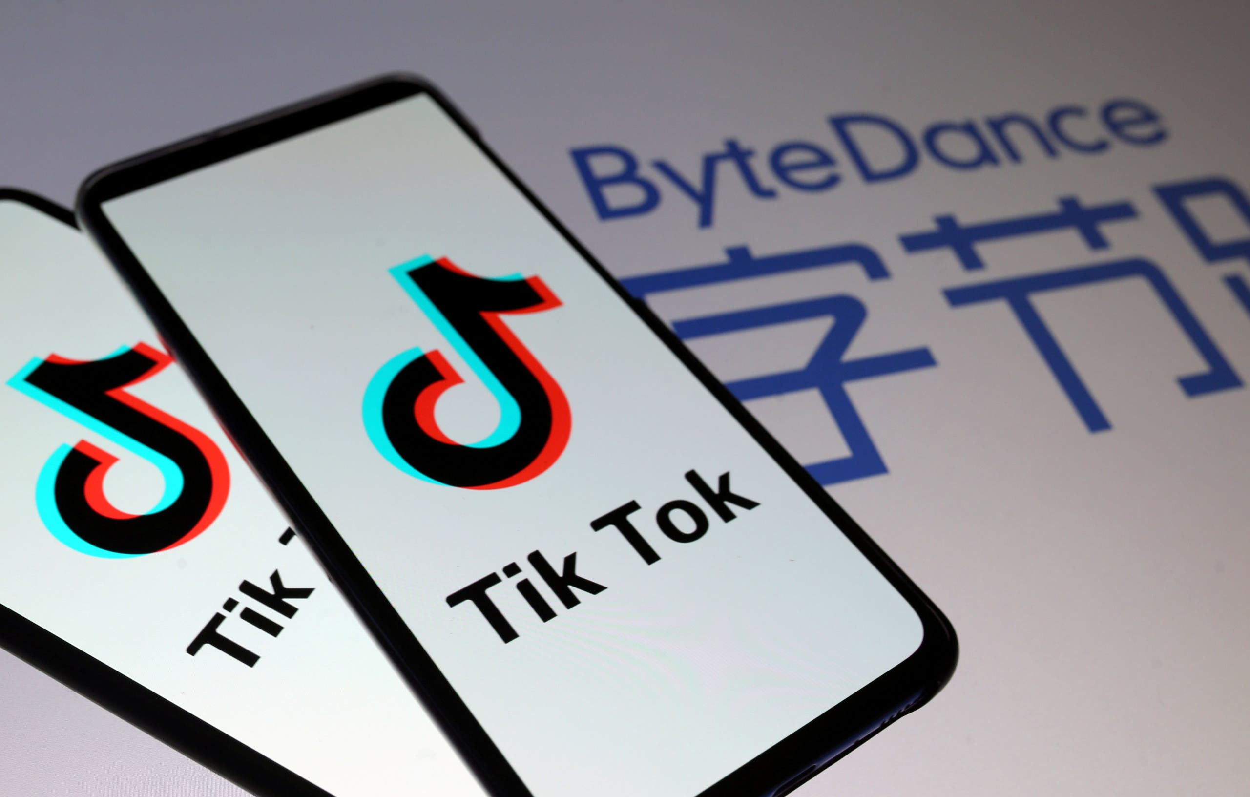 Tik Tok logos are seen on smartphones in front of a displayed ByteDance logo in this illustration. (Reuters)