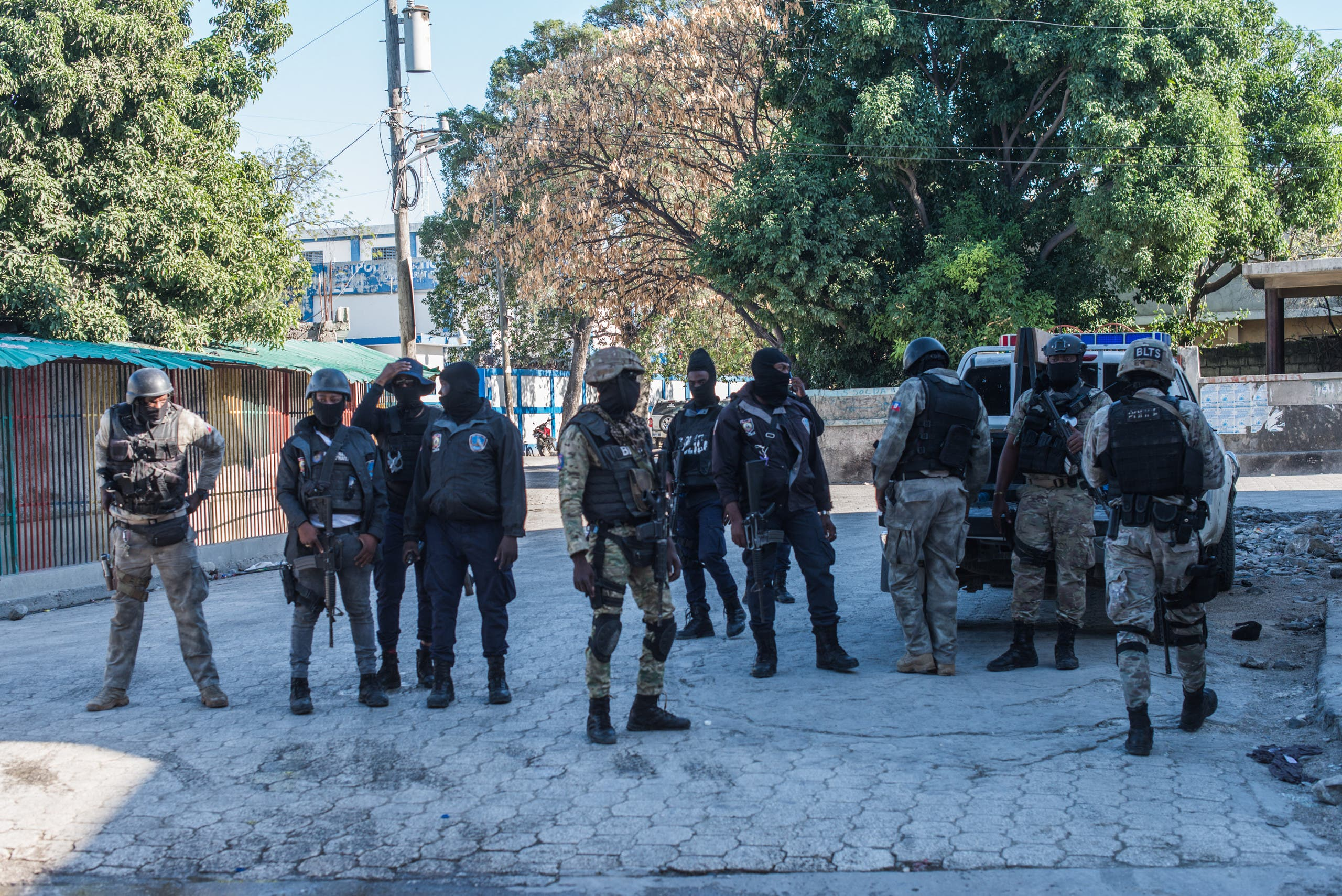 Several police officers from different specialized groups provide perimeter protection by the Croix-des-Bouquets prison from where many prisoners escaped and where several people were killed, in Croix-des-Bouquets, suburb of the Haitian capital, on February 25, 2021 AFP