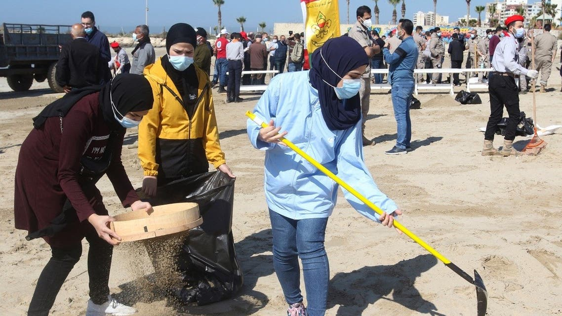 Young volunteers clean a contaminated beach in the southern Lebanese city of Tyre on February 27, 2021. (Mahmoud Zayyat/AFP)