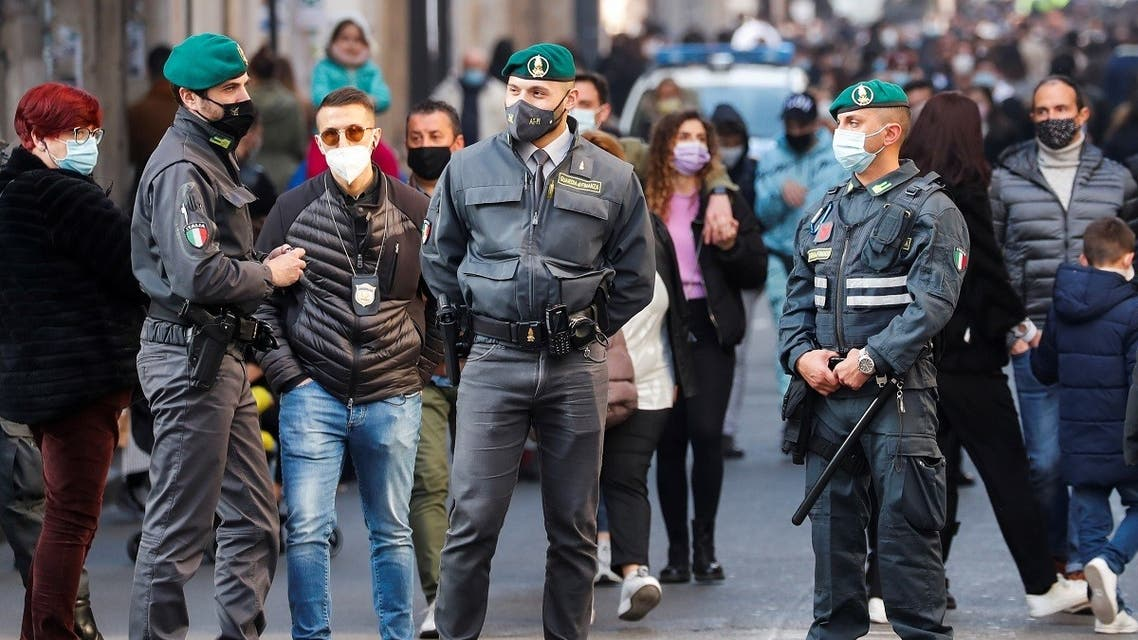 Security forces patrol as people wearing protective masks walk along the principal shopping street of Via del Corso, amidst the coronavirus outbreak, Rome, Italy, February 27, 2021. (Reuters/Remo Casilli)