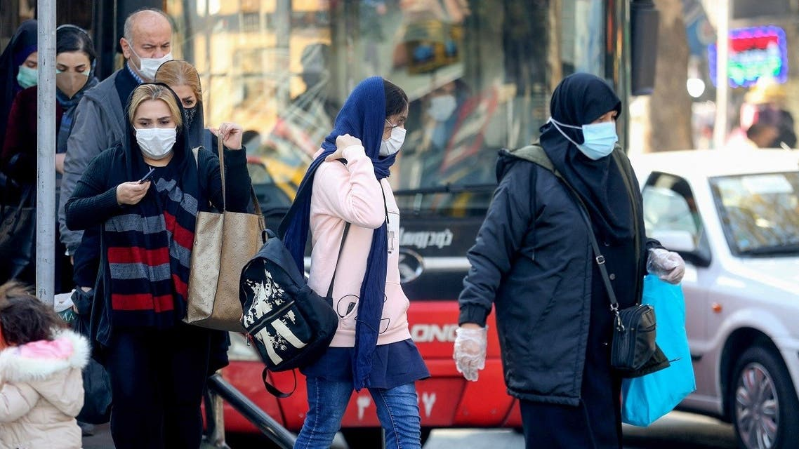 Iranians wearing protective masks amid the COVID-19 pandemic, leave a bus in the capital Tehran, on December 30, 2020. (Atta Kenare/AFP)