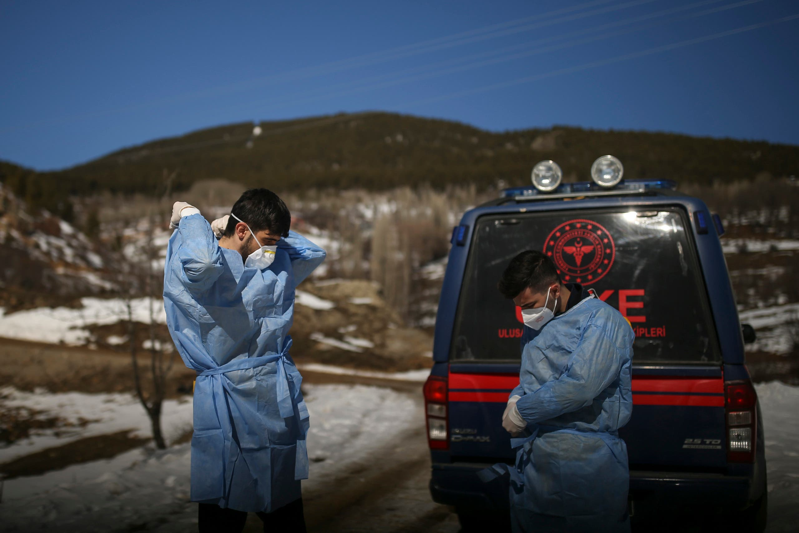 Dr. Yasin Kaya, left and health worker Yusuf Duran, right, members of the the Koyulhisar Public Health Center vaccination team, prepare to vaccinate 85-year-old Ibrahim Yigit in the isolated village of Gumuslu in the district of Sivas, central Turkey, Friday, Feb. 26, 2021. (AP)