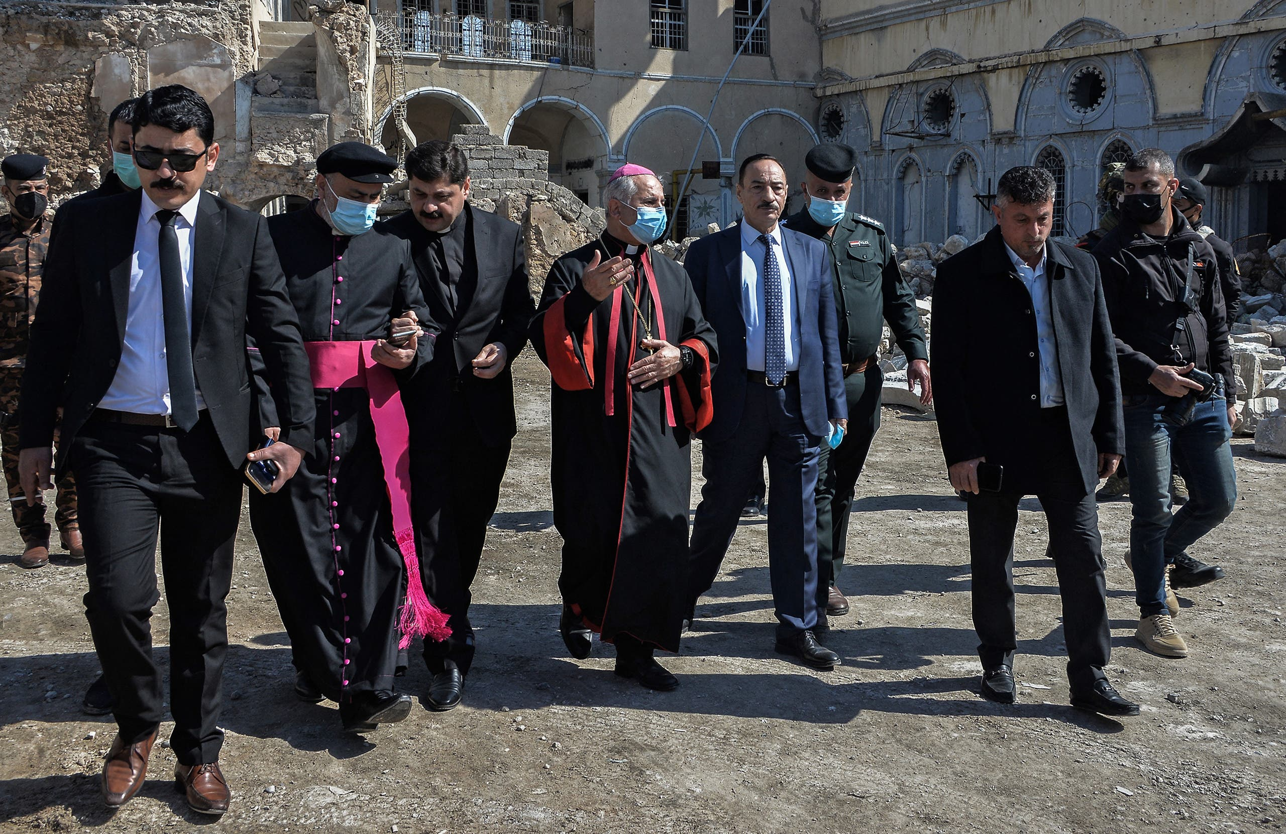 Archbishop of the Archeparchy of Mosul Najib Mikhael Moussa (C) and Father Raed Adel (C-L) and Niniveh Governor Najim al-Jabouri (C-R) escort the members of the Papal convoy during their visit to Iraq's northern city of Mosul, on February 23, 2021. (Zaid al-Obeidi/AFP)
