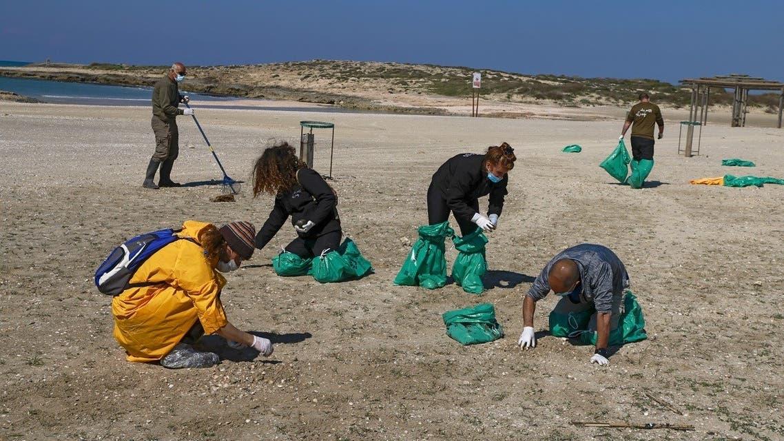 Israel volunteers clean the contaminated HaBonim beach, south the port city of Haifa, on February 21, 2021. (Menahem Kahana/AFP)