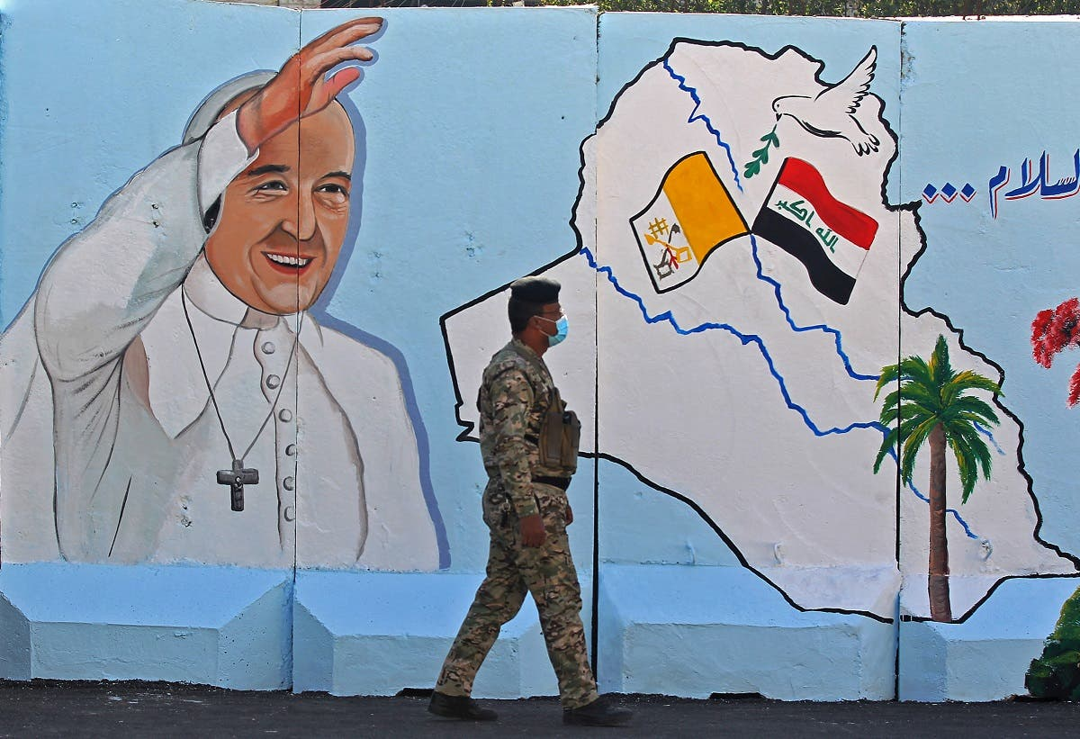 An Iraqi policeman walks by a mural depicting Pope Francis on the outer walls of Our Lady of Salvation (Sayidat al-Najat) Church, in Baghdad on February 22, 2021. (Ahmad al-Rubaye/AFP)