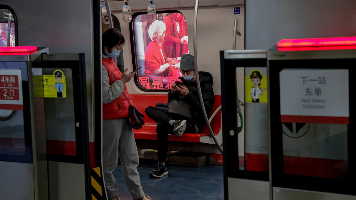Commuters wearing face masks to help curb the spread of the coronavirus browse their smartphones inside a subway train in Beijing Wednesday, Feb. 10, 2021. (AP)