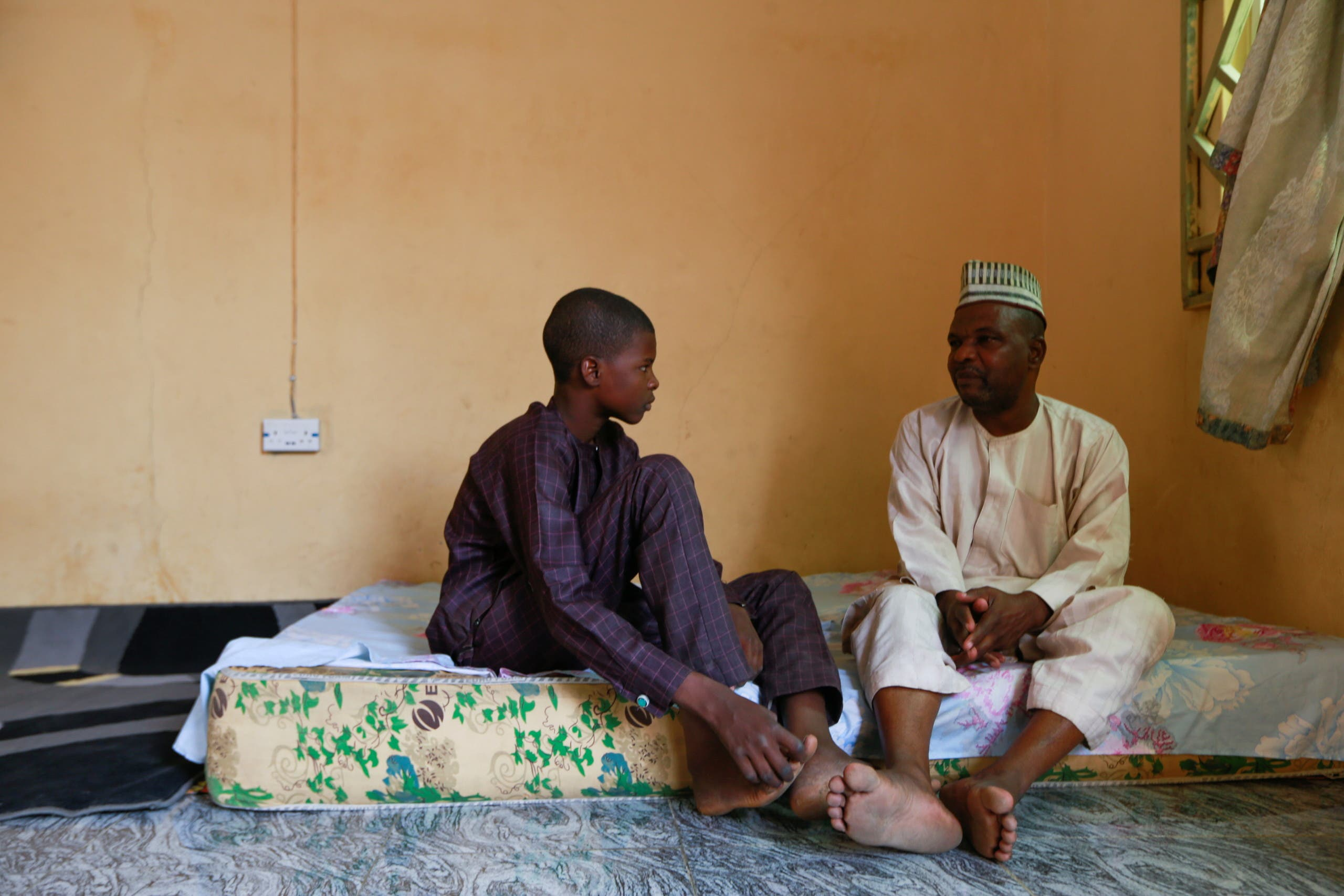 Balarabe Kagara speaks with one of his sons as the family awaits news of the release of two of his daughters after bandits kidnapped them from the JSS Jangebe school, in Zamfara, Nigeria February 28, 2021. (Reuters)