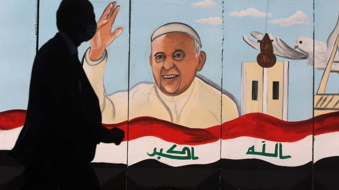 An Iraqi man walks by a mural depicting Pope Francis on the outer walls of Our Lady of Salvation (Sayidat al-Najat) Church, in Baghdad on February 22, 2021. (AFP)