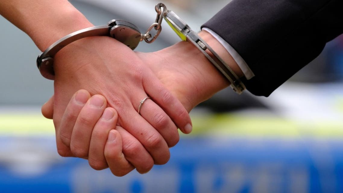 Young couple with hand-cuffs in front of a police car stock photo