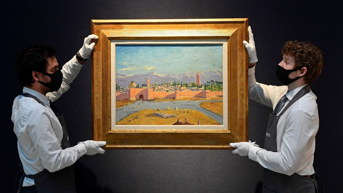 Art handlers pose with 'Tower of the Katoubia Mosque' painted by former British Prime Minister Winston Churchill in 1943, as preparations take place at Christie's ahead of a livestream auction of Modern British Art on March 1, in London, Britain, February 17, 2021. REUTERS/Toby Melville NO RESALES. NO ARCHIVES.