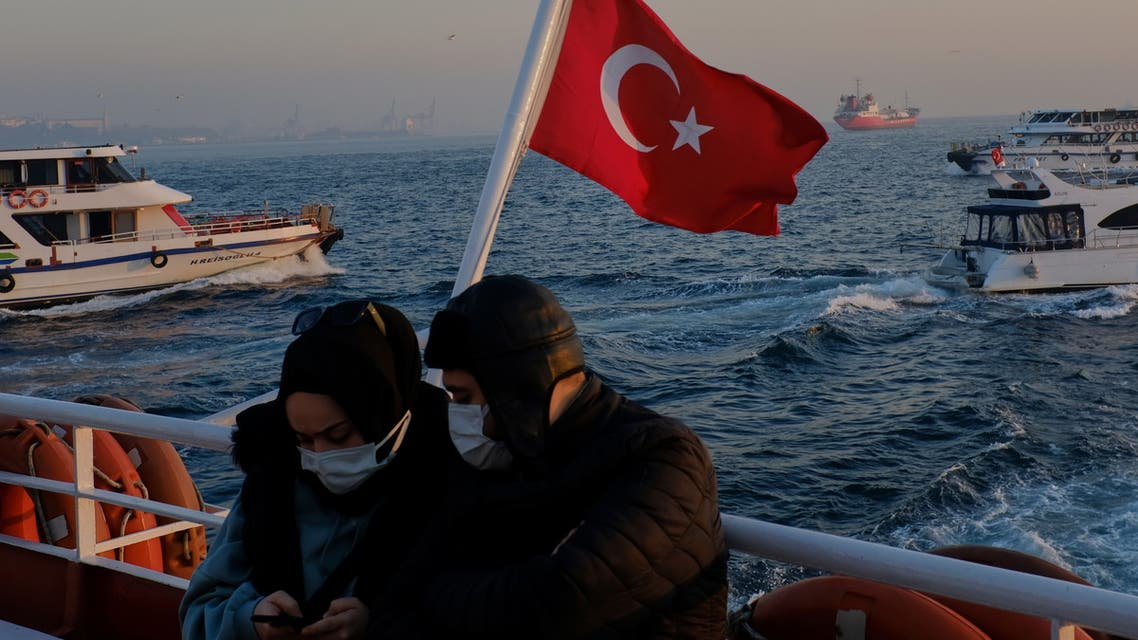 A couple wearing protective masks travel on a ferry over the Bosphorus, amid the coronavirus disease (COVID-19) outbreak in Istanbul, Turkey February 23, 2021. REUTERS/Murad Sezer