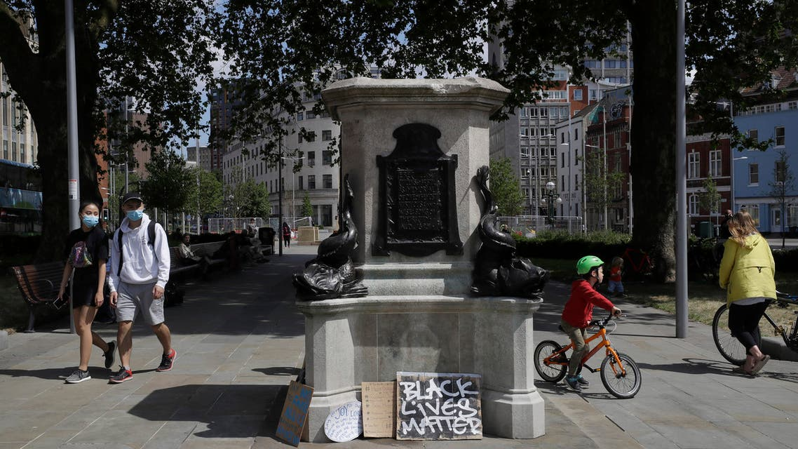 In this file photo dated Monday, June 8, 2020, people walk past the empty plinth after a statue of notorious slave trader Edward Colston was pulled down during a Black Lives Matter demo, in Bristol, England. (File photo: AP)