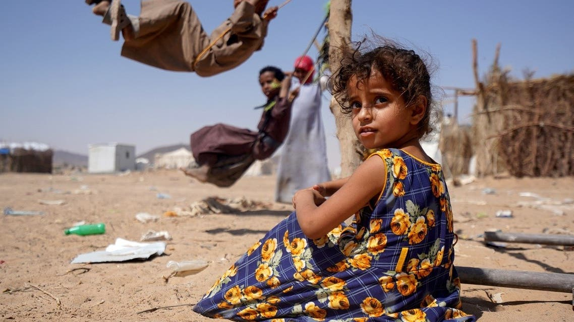 A girl sits as other children play on swings at a camp for internally displaced people in Marib, Yemen Feb. 16, 2021. (Reuters)