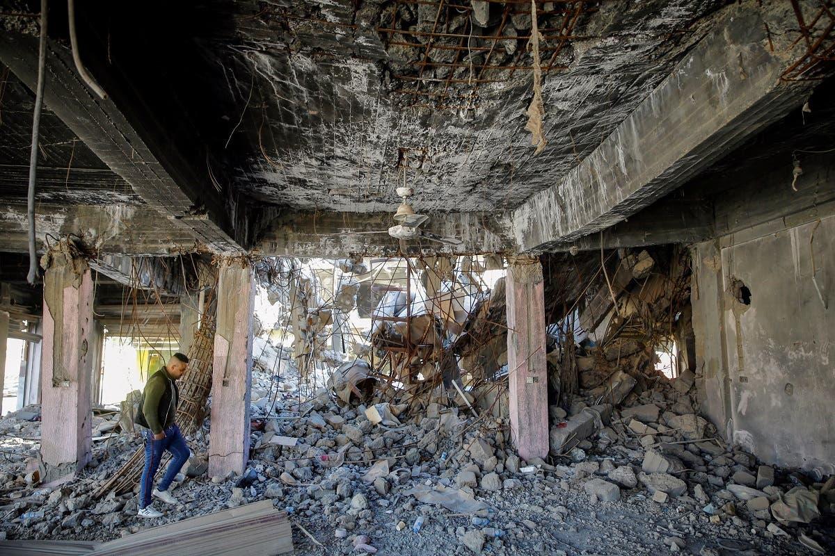 An Iraqi Christian man walks inside a damaged building during past fighting with Islamic State militants, in Qaraqosh, Iraq February 25, 2021. (Reuters/Thaier al-Sudani)