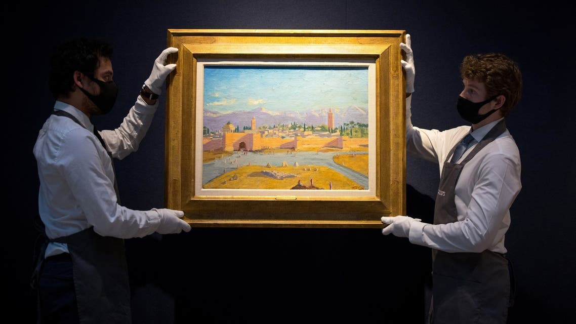 """In this file photo taken on February 17, 2021 gallery workers pose with an artwork titled """"Tower of Koutoubia Mosque"""" by Winston Churchill during a photocall at Christie's auction house in London. (AFP)"""