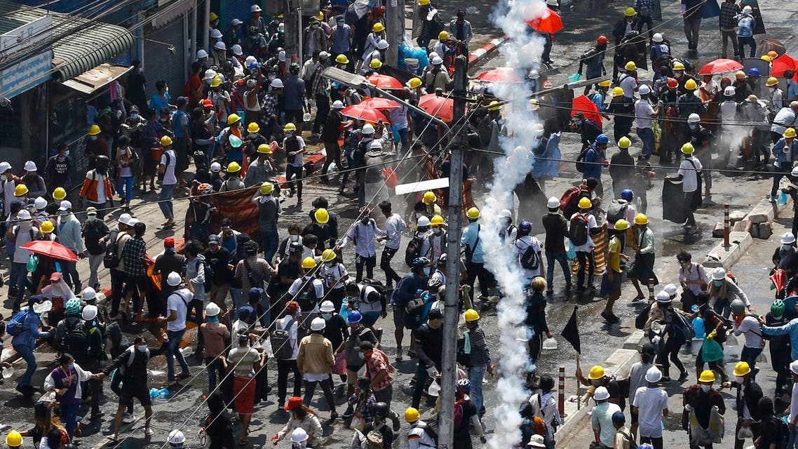 Protesters run as tear gas is fired during a demonstration against the military coup in Yangon on March 1, 2021. (File photo: AFP)
