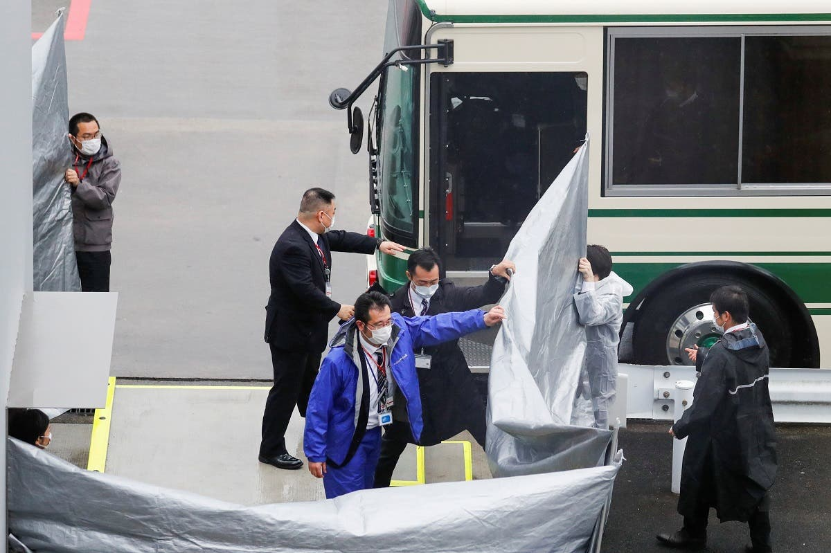 Japanese officers get prepared to escort US citizens Michael Taylor and his son Peter Taylor, suspected of helping former Nissan Motor Chairman Carlos Ghosn to escape to Lebanon, upon their arrival at Narita airport, following their extradition to Japanese Prosecutors, in Chiba, Japan, on March 2, 2021. (Reuters)