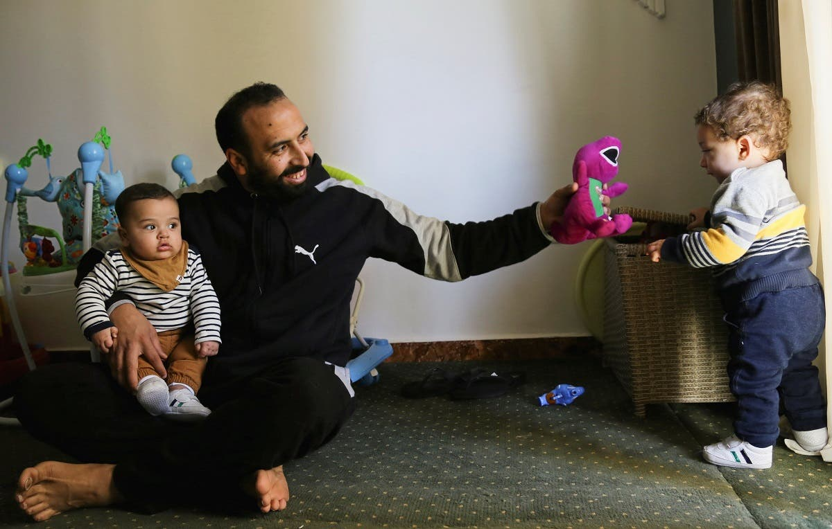 Mohamed Abdallah holds his biological son Soliman as he plays with Dawood, an orphan he sponsors, in their home in Cairo, Egypt February 24, 2021. Picture taken February 24, 2021. (Reuters/Hanaa Habib)
