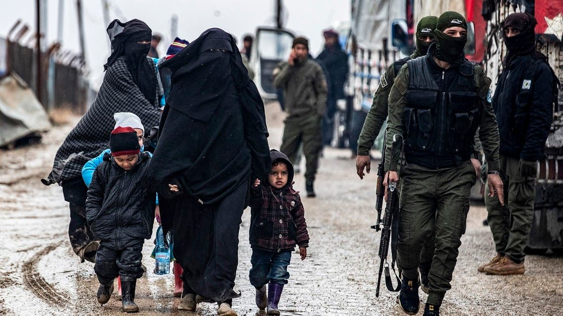 A veiled woman walks with children next to a member of the Syrian Kurdish internal security services known as Asayish at al-Hol camp in Hasakeh governorate in northeastern Syria, on January 19, 2021.  (Delil Souleiman/AFP)
