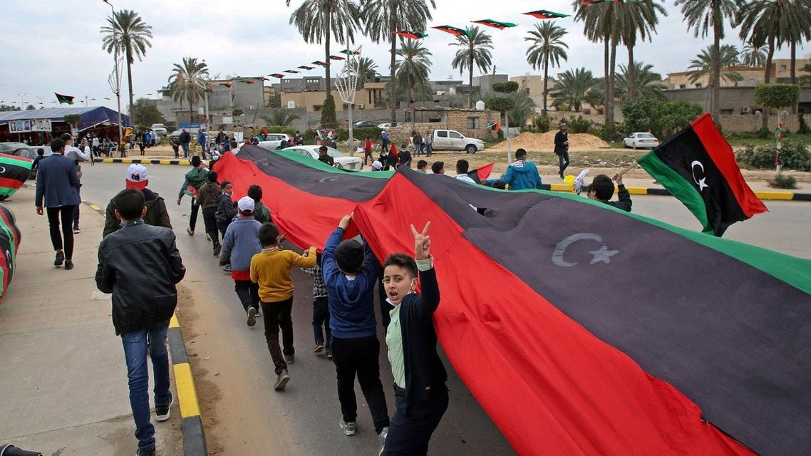 Libyan youth march with a giant national flag in the capital Tripoli on February 25, 2021, during celebrations commemorating the 10th anniversary of the 2011 revolution that toppled longtime dictator Muammar Gaddafi. (Mahmud Turkia/AFP)