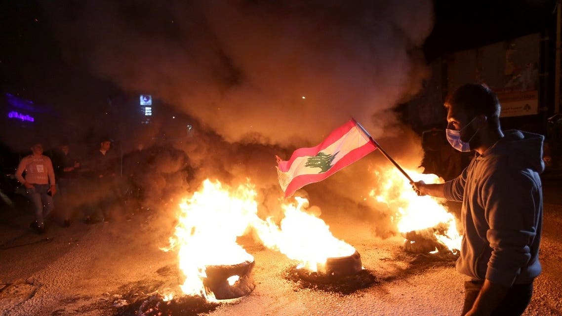 A demonstrator holds a Lebanese flag as he stands near burning tires during a protest against the fall in Lebanese pound currency and mounting economic hardship, March 2, 2021. (Reuters)