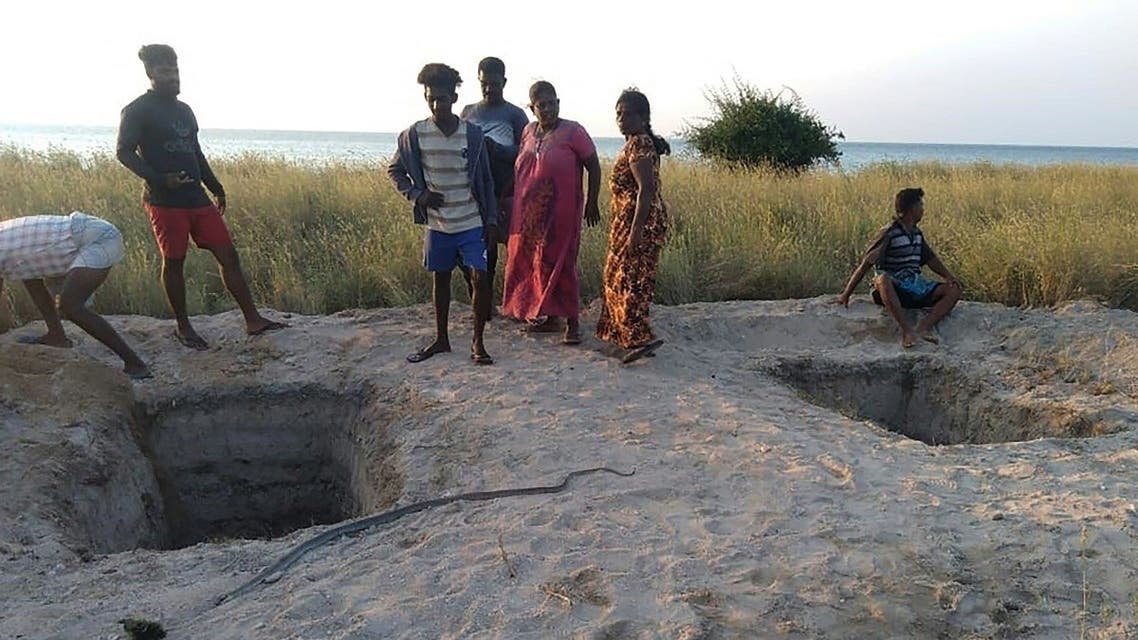 Local residents stand next to graves dug by the authorities to bury coronavirus victims after the government announced reversing its policy of forced cremations, at the islet of Iranaitivu off Sri Lanka's northern province, March 2, 2021. (AFP)