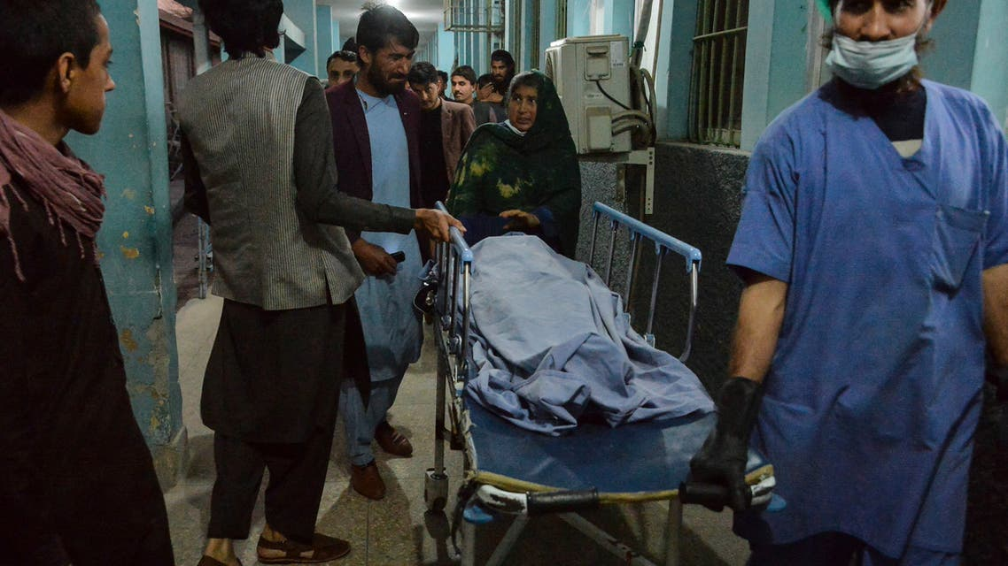 Hospital workers and relatives shift the body of one of the three female media workers shot to death in two separate attacks, at a hospital in Jalalabad on March 2, 2021. (AFP)