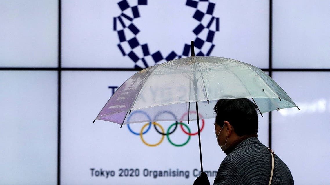 A man wearing a protective face mask walks past in front of a display showing the logo of Tokyo 2020 Olympic Games that have been postponed to 2021 due to the coronavirus disease (COVID-19) outbreak, in Tokyo, Japan, on January 23, 2021. (Reuters)