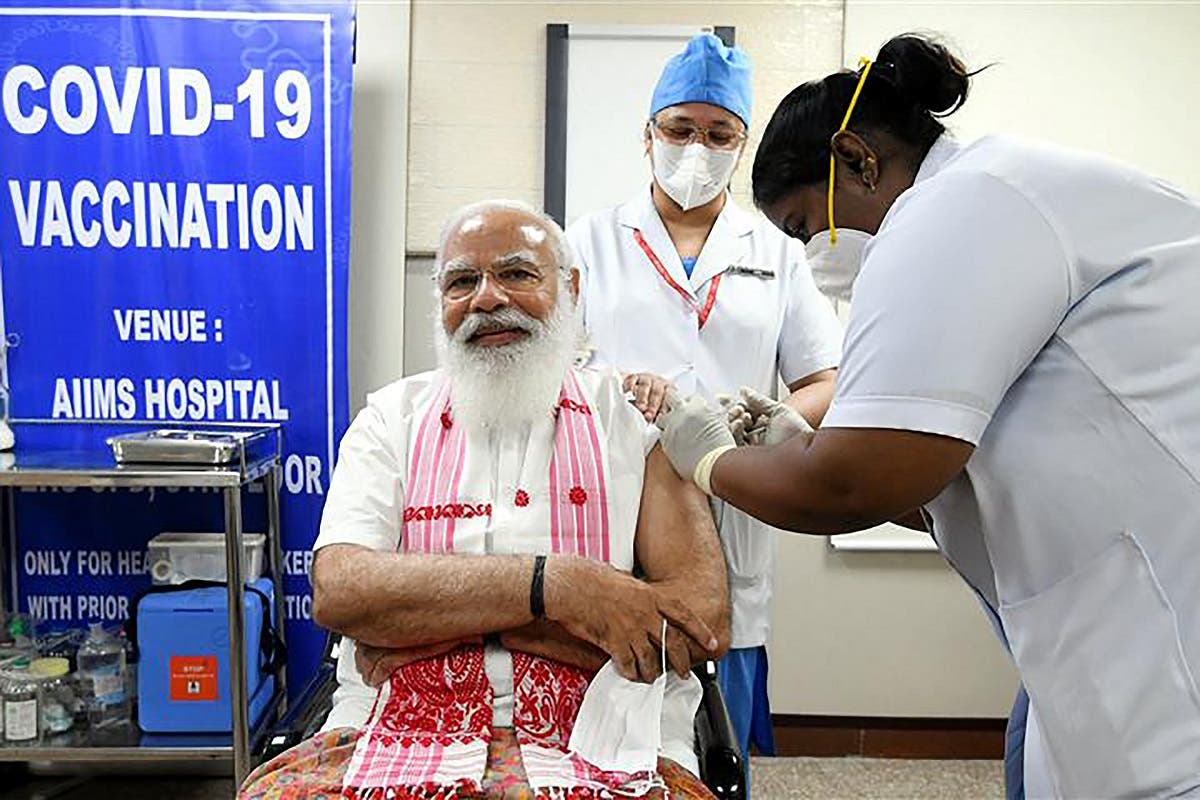 In this handout photograph taken on March 1, 2021 and released by the Indian Press Information Bureau (PIB), a health worker inoculates India's PM Modi (L) with COVAXIN coronavirus vaccine at AIIMS hospital in New Delhi. (PIB/AFP)