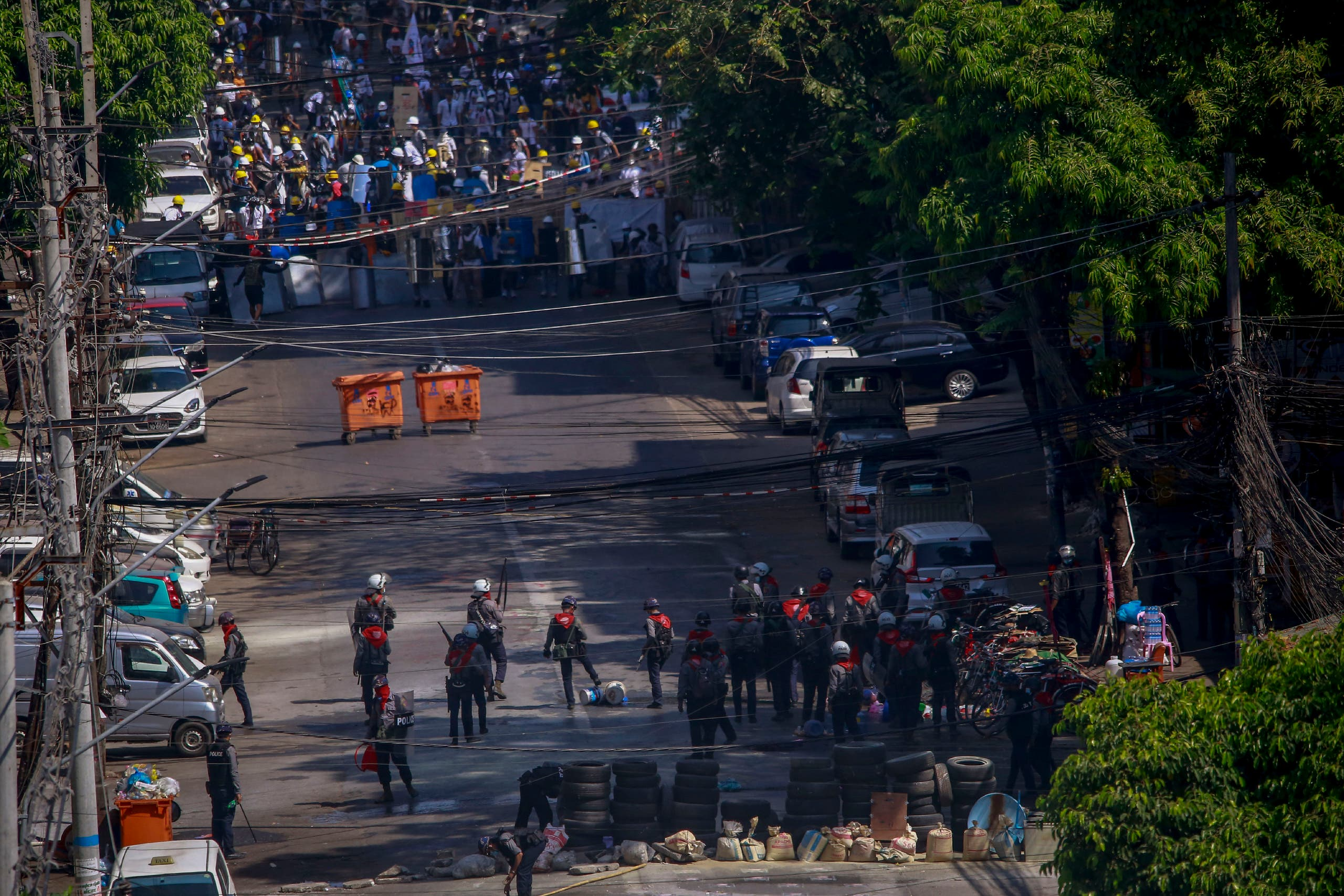 Anti-coup protesters standing behind barricades standoff with a group of police in Yangon, Myanmar Thursday, March 4, 2021. (AP)