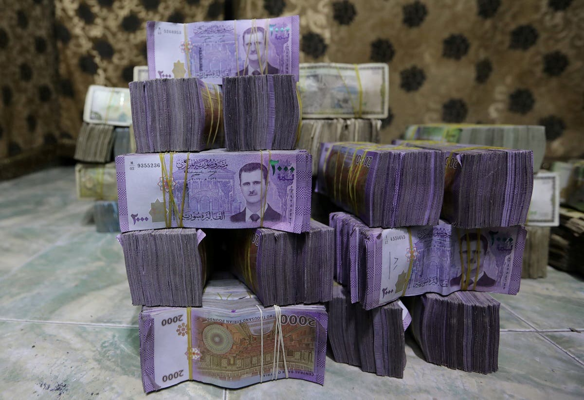Stacks of Syrian pounds are pictured inside an exchange currency shop in Azaz, Syria, on February 3, 2020. (Reuters)