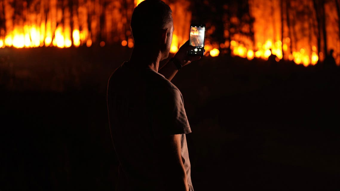A man takes photos of a fire outside the village of Roqueiro, near Oleiros, Portugal, Monday, Sept. 14, 2020. (File photo: AP)