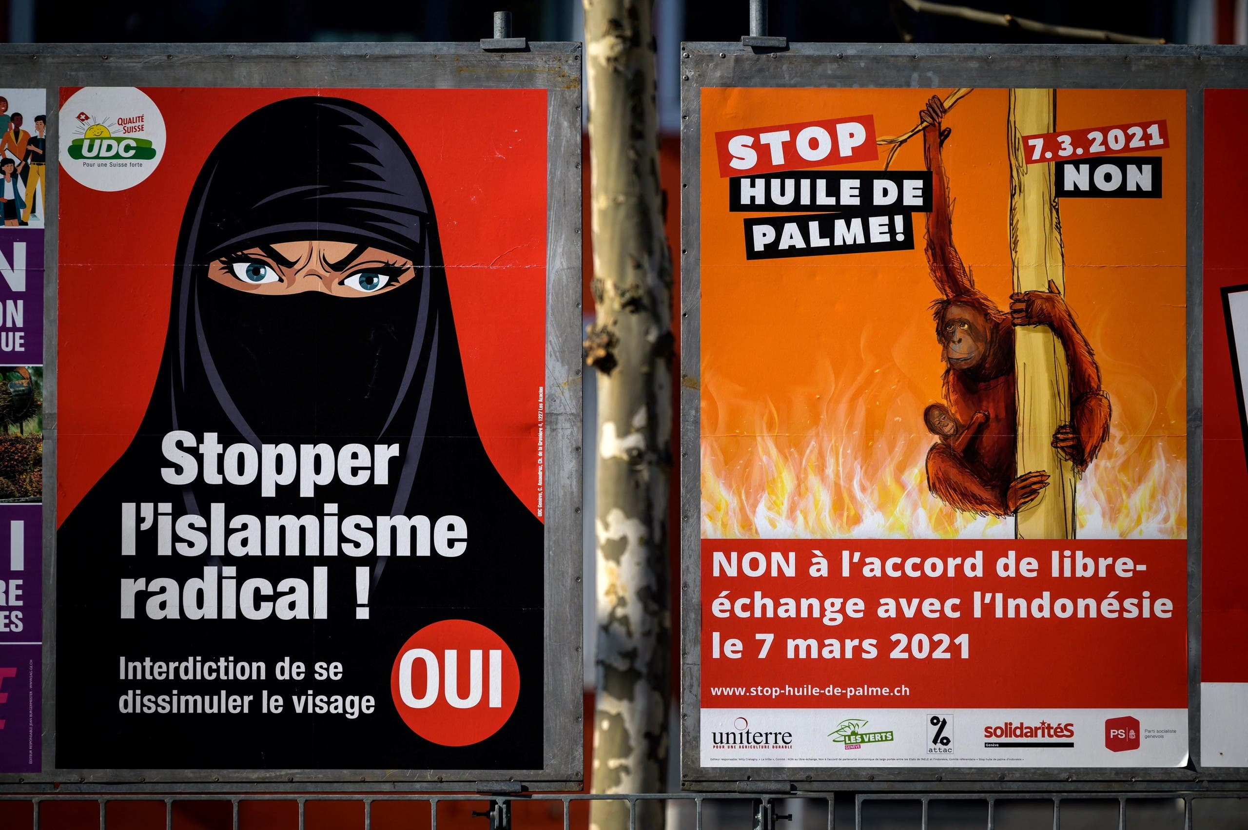 A photograph taken on March 1, 2021 in Geneva shows two campaign posters, one in favor of a burqa ban (L) and the other (R) against a free trade agreement with Indonesia on March 7, 2021 ahead of a nationwide vote. (AFP)
