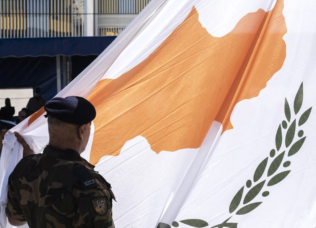 عنصر من الأمن القبرصي أمام علم بلاده - أرشيفية فرانس برس