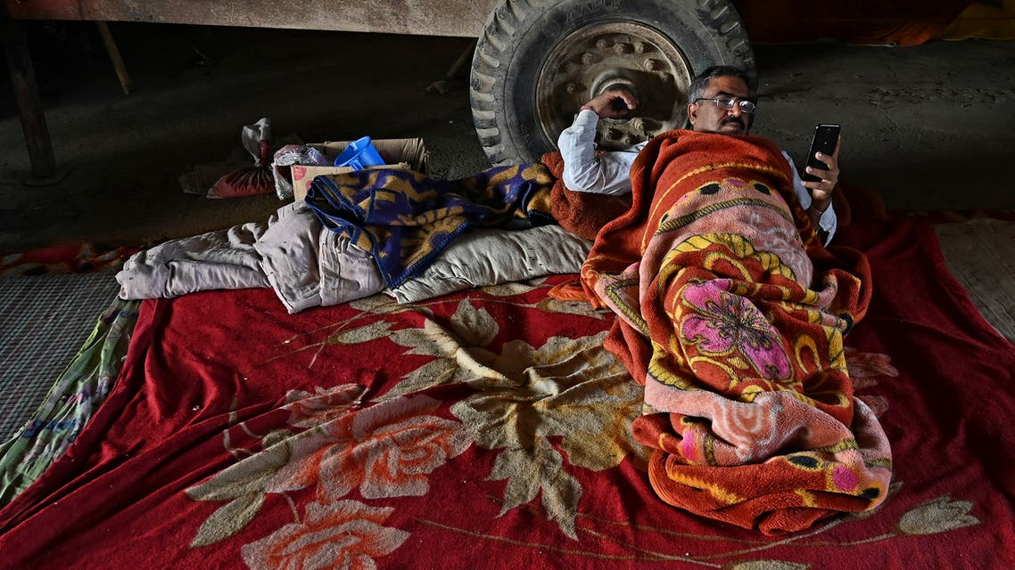 A Protesting farmer checks his mobile phone as he rests along a blocked highway as farmers continue the protest against the central government's recent agricultural reforms at Gazipur Delhi-Uttar Pradesh state border, in Ghaziabad on March 5, 2021. (AFP)