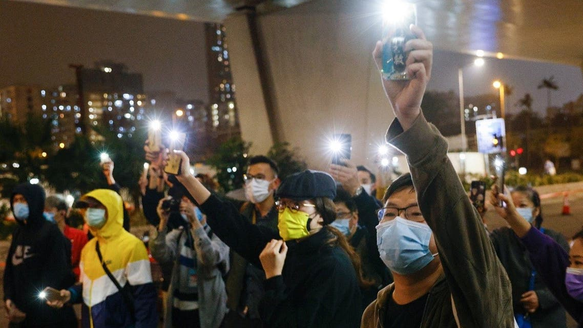 Supporters of 47 pro-democracy activists hold flashlights as they wait for four of them to leave the West Kowloon Magistrates' Courts on bail, over a national security law charge, in Hong Kong, China, on March 5, 2021. (Reuters)