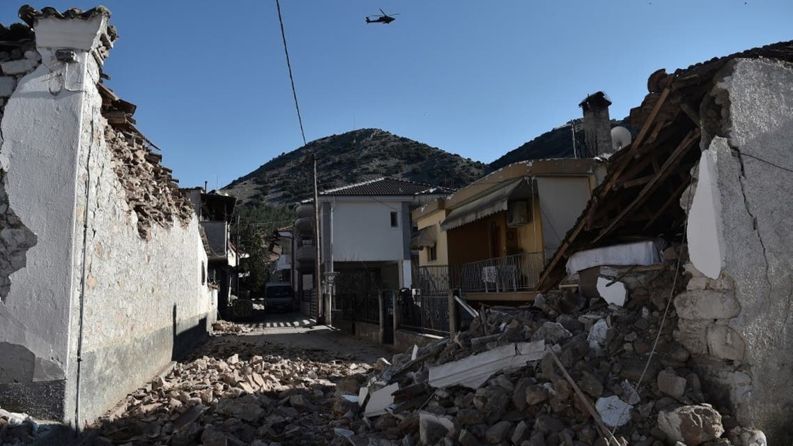 An army helicopter flies over collapsed buildings in the village of Damasi, near the town of Tyrnavos, after a strong 6,3-magnitude earthquake hit the Greek central region of Thessaly on March 3, 2021. (AFP)