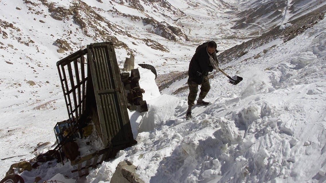 An Afghan driver clears snow from around his truck after it was swept off the road by an avalance on the south side of Salang tunnel, some 100 km north from Kabul. (File photo: Reuters)