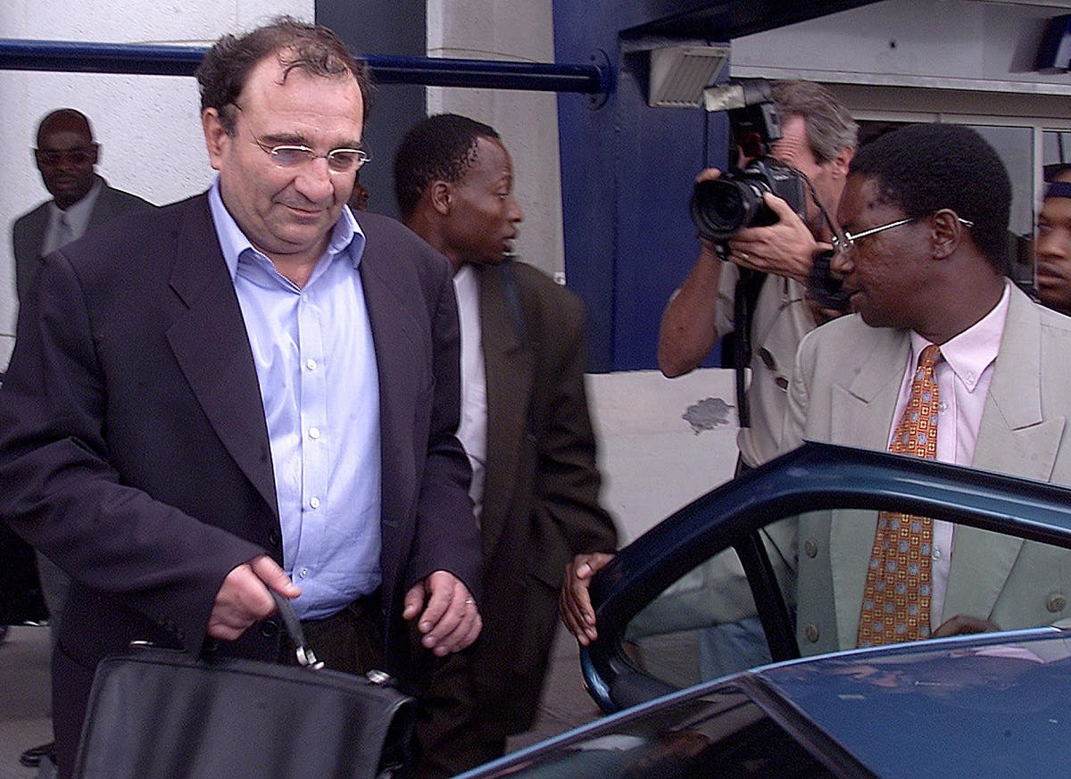 A file photo shows Ari Ben Menashe, an Israeli-Canadian consultant, is hustled into a car by Zimbabwe security personnel shortly after his arrival at Harare International Airport, Friday Feb. 22, 2002. (AP)