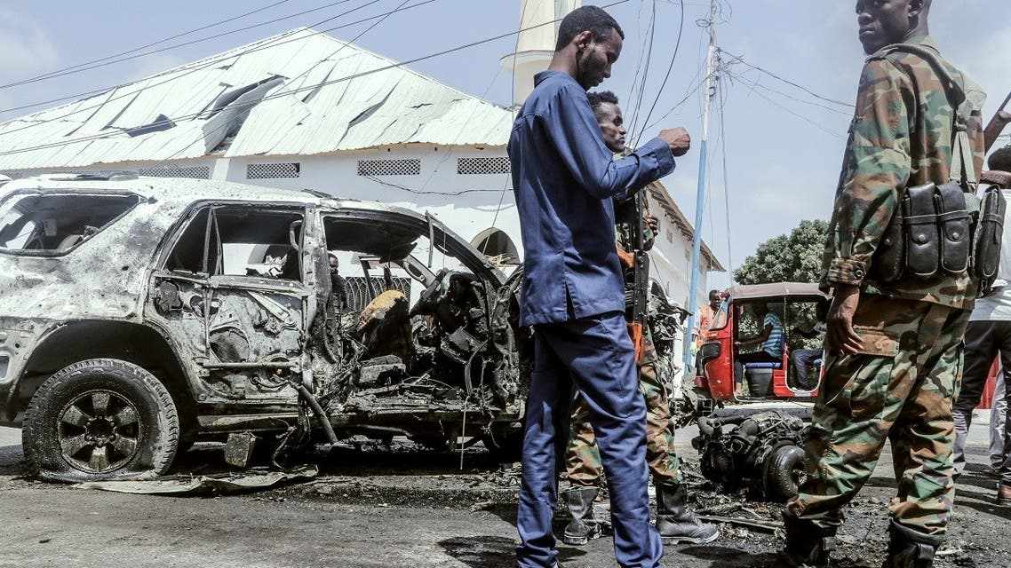 Officials gather beside debris at the site of a suicide car bombing attack near a security checkpoint in Mogadishu on February 13, 2021. (AFP)