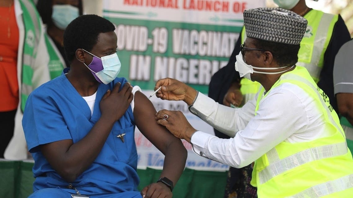 Dr. Ngong Cyprian (L), the first Nigerian to receive the first dose of the Oxford/AstraZeneca vaccine at the National Hospital Abuja, Nigeria on March 5, 2021. (Kola Sulaimon/AFP)