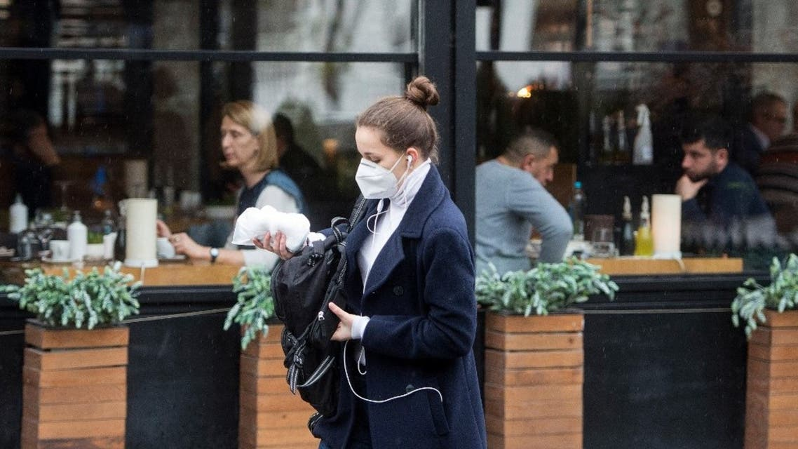 A woman, wearing a protective mask, walks past an opened restaurant in downtown Skopje on February 11, 2021. (AFP)