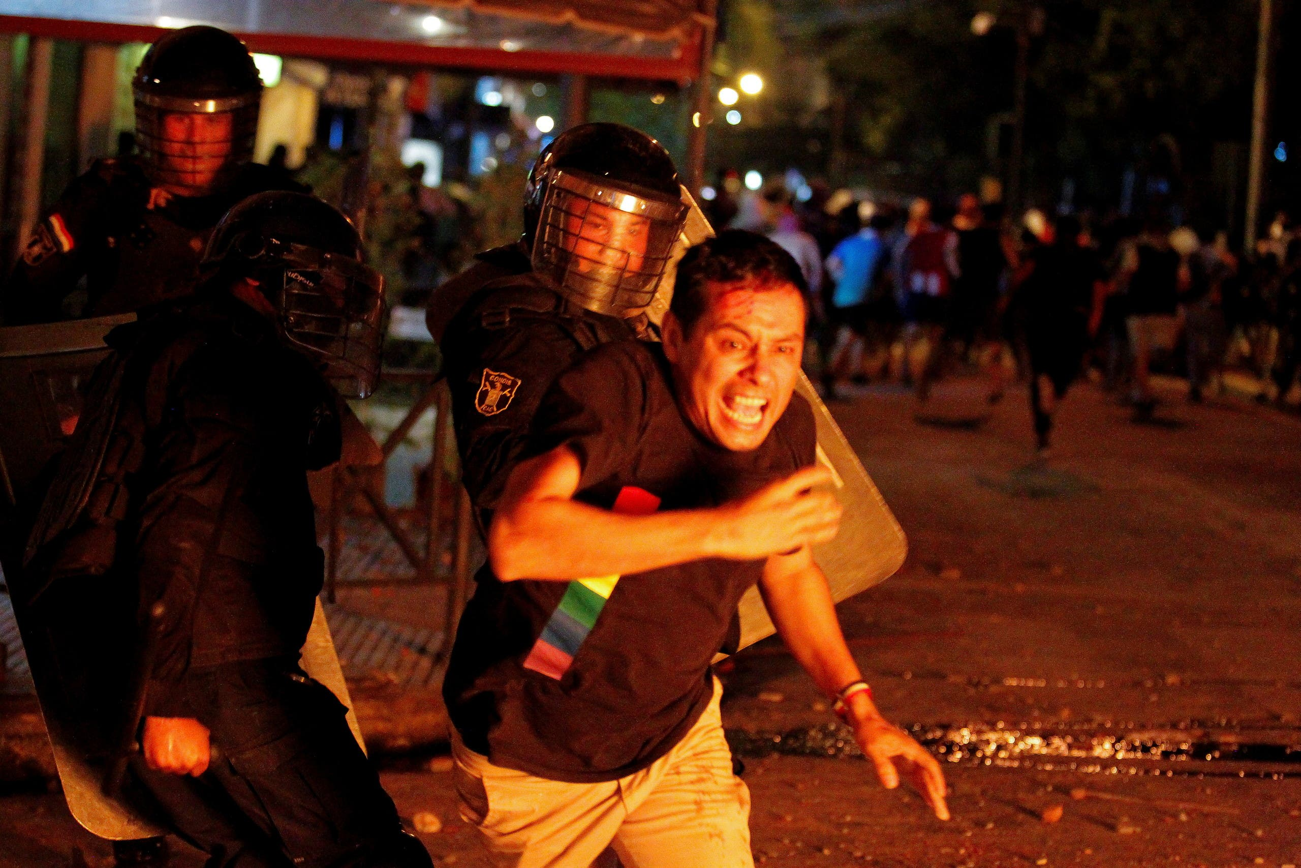 Riot police officers clash with a demonstrator during a protest against President Mario Abdo Benitez's health policies and the lack of coronavirus disease (COVID-19) vaccines in Asuncion, Paraguay March 5, 2021. (Reuters)