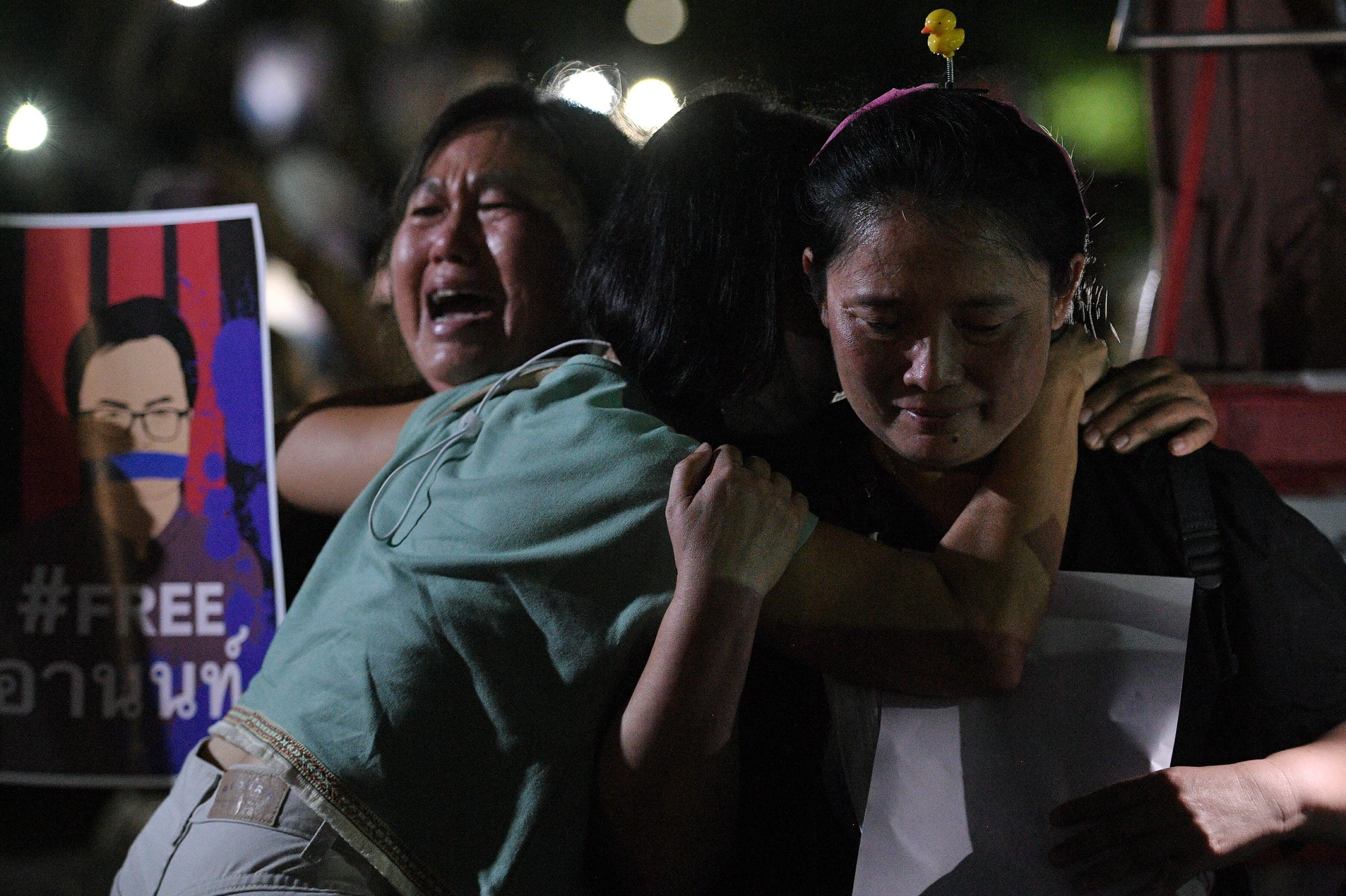 Anti-government demonstrators embrace each other as they gather inside Kasetsart University, calling authorities to release four protestors including Parit Penguin Chiwarak and Anon Numpa charged with lese majeste law in Bangkok, Thailand March 6, 2021. (Reuters)
